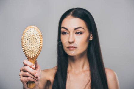 upset brunette woman holding hairbrush isolated on grey, hair loss concept