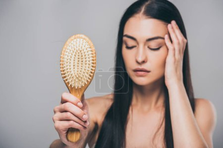 stressed brunette woman with closed eyes holding hairbrush isolated on grey, hair loss concept