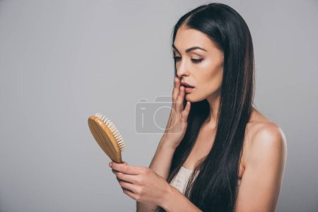 shocked young brunette woman holding hairbrush isolated on grey, hair loss concept