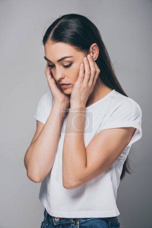 sad brunette woman with hands on face looking down isolated on grey