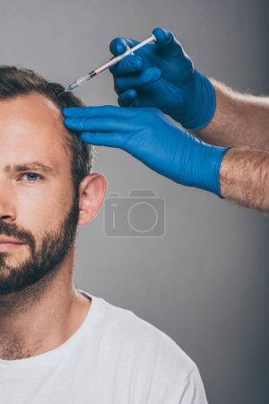 cropped shot of doctor with syringe giving injection to man with alopecia looking at camera isolated on grey