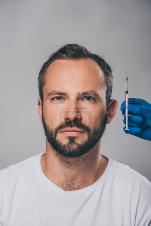 cropped shot of doctor holding syringe and man with alopecia looking at camera isolated on grey