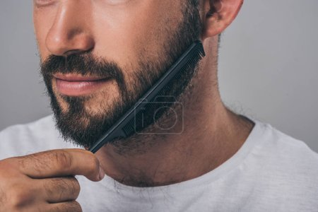 cropped shot of bearded man combing beard with comb isolated on grey