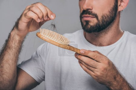 cropped shot of bearded man holding hairbrush, hair loss concept