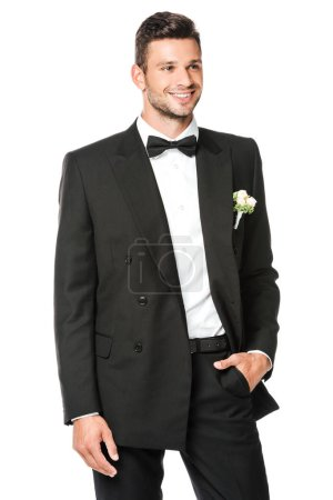 smiling groom buttoning suit and looking away isolated on white