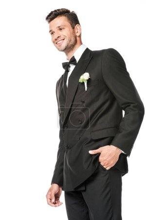 smiling young groom in stylish suit with boutonniere isolated on white