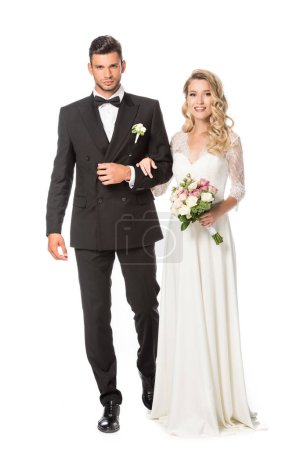 happy young bride and groom walking together and looking at camera isolated on white