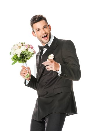 happy young groom with bridal bouquet pointing at camera isolated on white