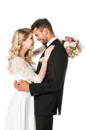 happy newlyweds embracing and looking at each other isolated on white