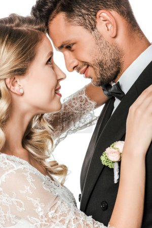 close-up portrait of young bride and groom embracing and looking at each other isolated on white