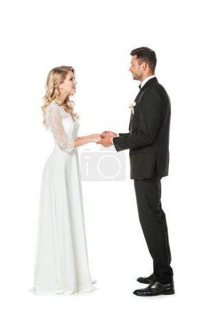 happy young bride and groom holding hands and looking at each other isolated on white