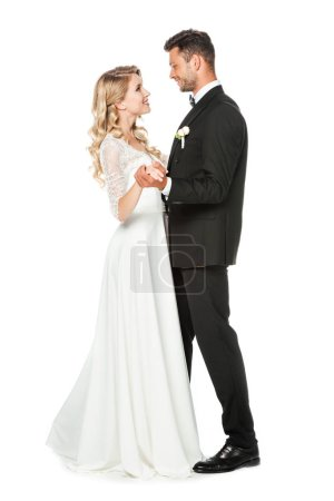 beautiful young bride and groom dancing and looking at each other isolated on white