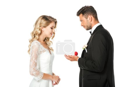 side view of groom showing wedding rings to bride isolated on white