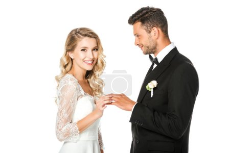 happy young bride putting on wedding ring on grooms finger isolated on white