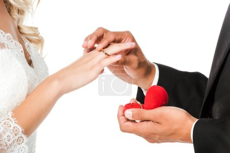 cropped shot of groom putting on wedding ring on brides finger isolated on white
