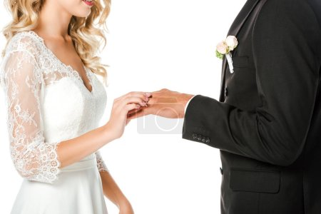 cropped shot of young bride putting on wedding ring on grooms finger isolated on white