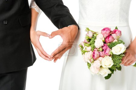 cropped shot of bride with bouquet and groom making heart sign with hands isolated on white