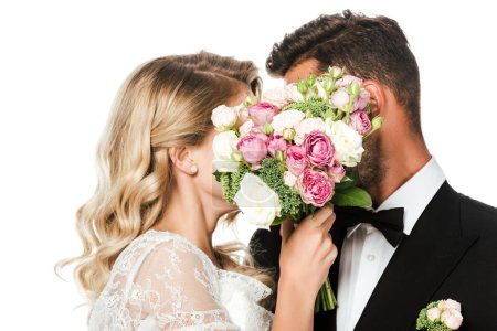 young bride and groom covering faces with bridal bouquet isolated on white