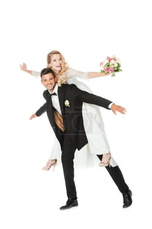 happy young bride piggybacking on groom isolated on white
