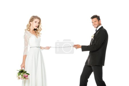happy young groom with chain and leashed bride isolated on white