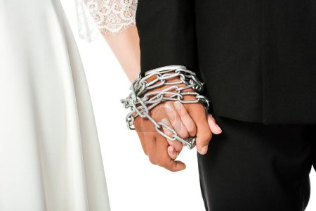 cropped shot of bride and groom holding hands tied in chain isolated on white
