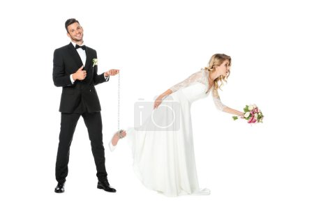 happy groom holding chain tied around brides leg and showing thumb up isolated on white