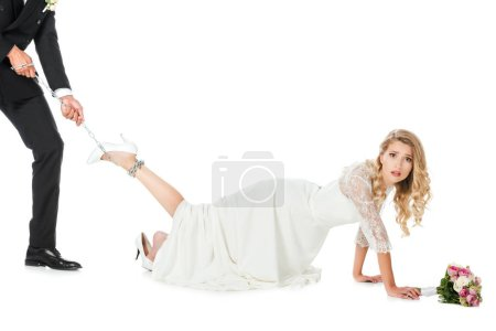 cropped shot of groom holding chain tied around shocked brides leg isolated on white