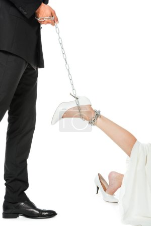 cropped shot of groom holding chain tied around brides leg isolated on white