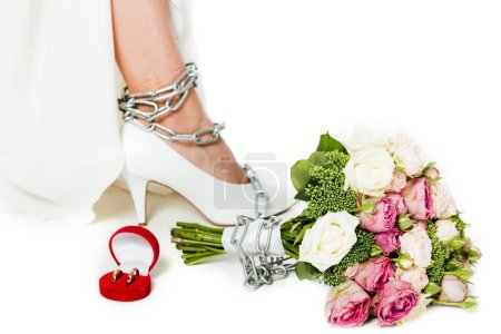 cropped shot of bride with leg tied in chain standing near bouquet and wedding rings isolated on white