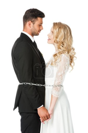 beautiful young newlyweds tied with chain and looking at each other  isolated on white