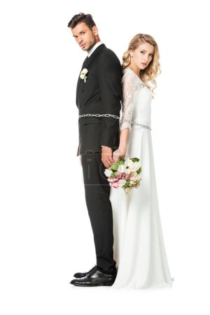 serious young newlyweds tied with chain back to back and looking at camera isolated on white