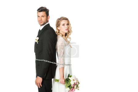 young newlyweds tied with chain back to back and looking at camera isolated on white