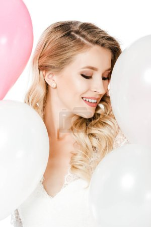 smiling young bride surrounded with white and pink balloons isolated on white
