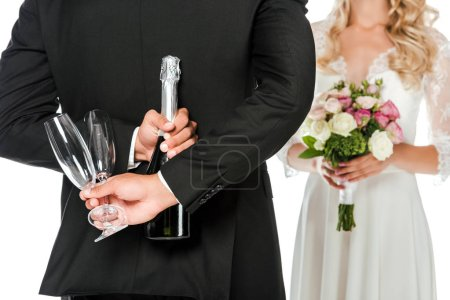 cropped shot of groom holding champagne bottle and glasses behind back while bride standing in front of him isolated on white