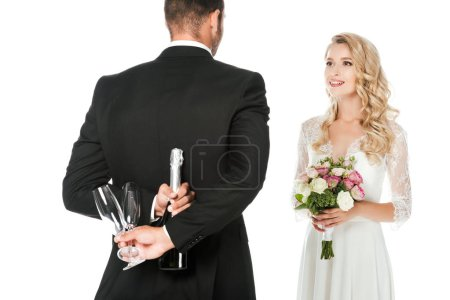 rear view of groom holding champagne bottle and glasses behind back while bride standing in front of him isolated on white