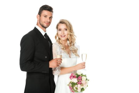 happy young newlyweds with champagne glasses looking at camera isolated on white