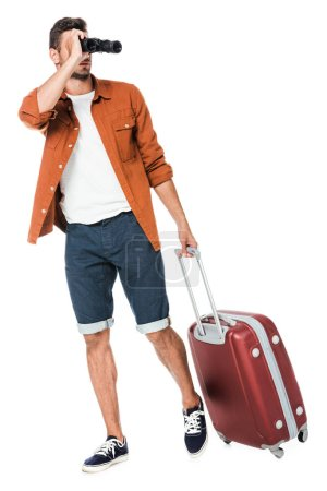 happy young man with binoculars and luggage walking and looking away isolated on white