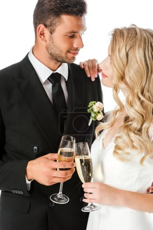 beautiful young bride and groom clinking glasses of champagne isolated on white