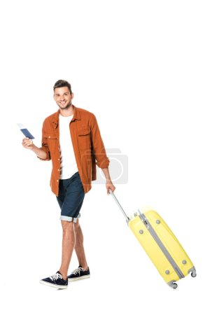 happy young man with luggage and flight ticket walking and looking at camera isolated on white