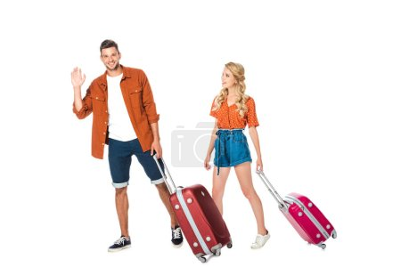 happy young couple with luggage walking and waving at camera isolated on white