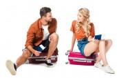 couple souriant, assis sur les valises avec les passeports et les billets isolés sur blanc