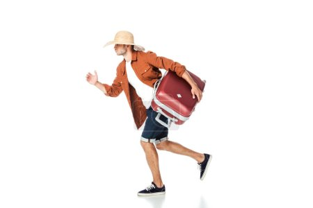 side view of tourist in straw hat running with travel bag isolated on white
