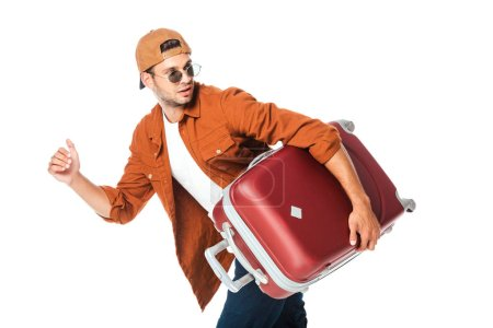 side view of handsome tourist running with travel bag isolated on white