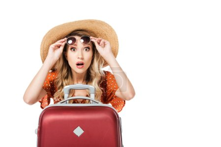 Photo for Shocked beautiful girl holding sunglasses and sitting near travel bag isolated on white - Royalty Free Image