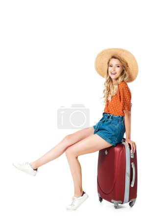 Photo for Beautiful girl sitting on travel bag and looking at camera isolated on white - Royalty Free Image