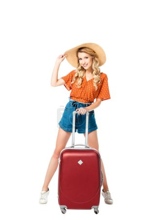 beautiful girl in straw hat posing with travel bag isolated on white
