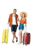 smiling couple standing with travel bags and clinking with glasses of champagne isolated on white