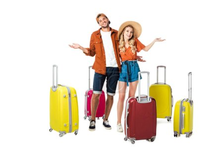 smiling newlywed couple with arranged suitcases around isolated on white