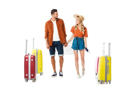 newlywed couple holding hands and looking at each other with suitcases around isolated on white