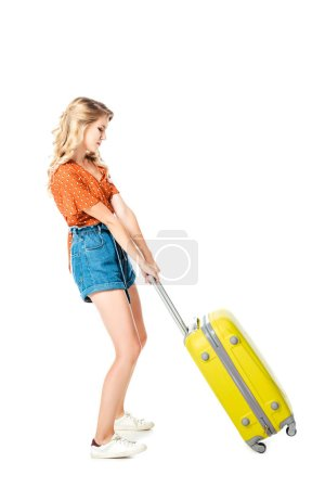 young woman pulling heavy yellow suitcase alone isolated on white